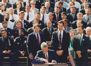 Flanked by Law Enforcement, President Bill Clinton signs into law the 1994 Crime Bill. Then-First Lady Hillary Clinton sits behind him, on the front row.