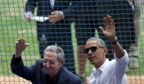 U.S. President Barack Obama, right, and his Cuban counterpart Raul Castro wave to cheering fans as they arrive for a baseball game between the Tampa Bay Rays and the Cuban national baseball team, in Havana, Cuba, Tuesday, March 22, 2016. The crowd roared as Obama and Cuban President Raul Castro entered the stadium and walked toward their seats in the VIP section behind home plate. It's the first game featuring an MLB team in Cuba since the Baltimore Orioles played in the country in 1999. (AP Photo/Rebecca Blackwell)